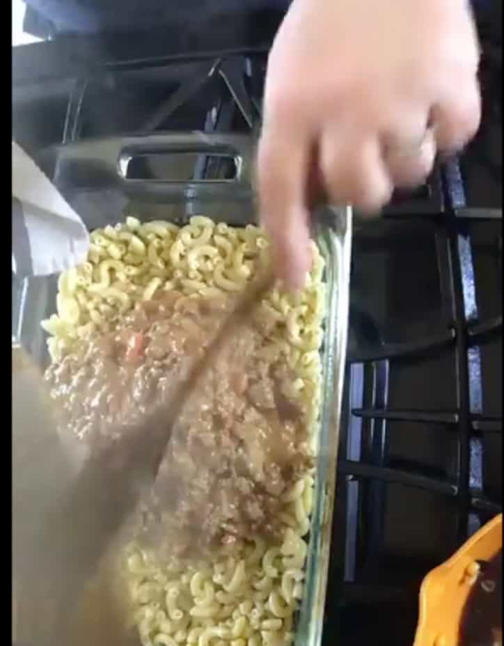 ground beef and cheese added over the top of macaroni noodles in pan