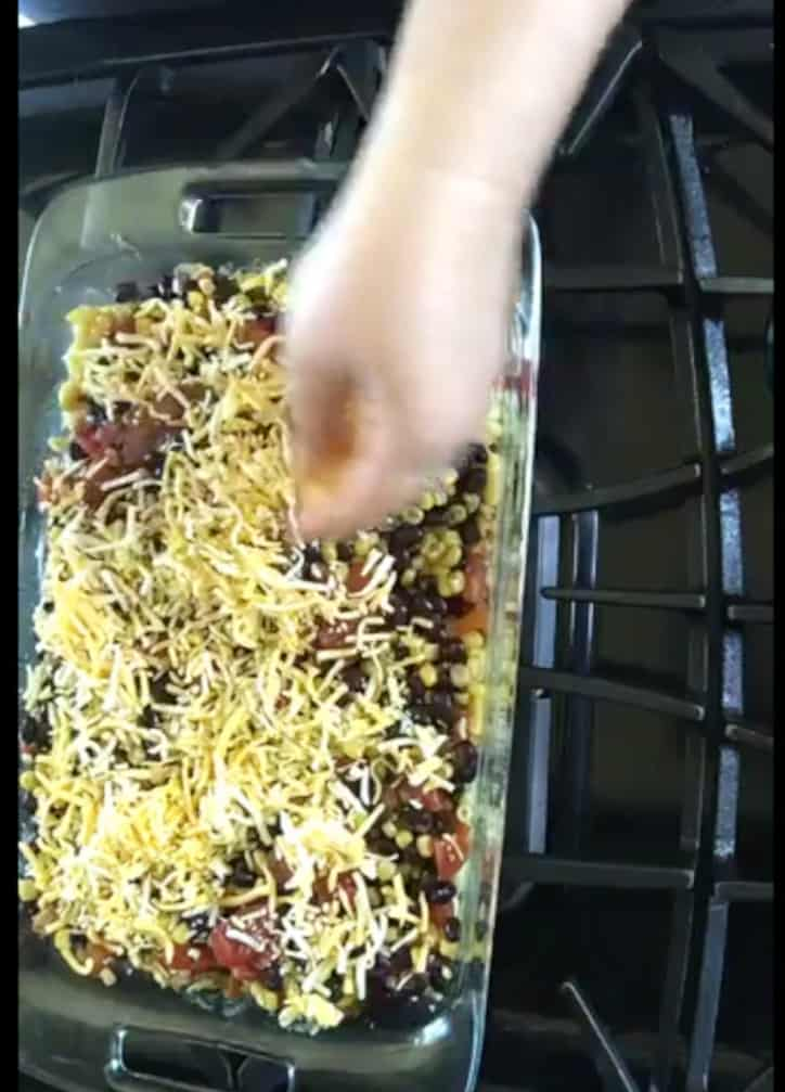 hand spreading shredded cheddar cheese over the top of easy taco bake casserole