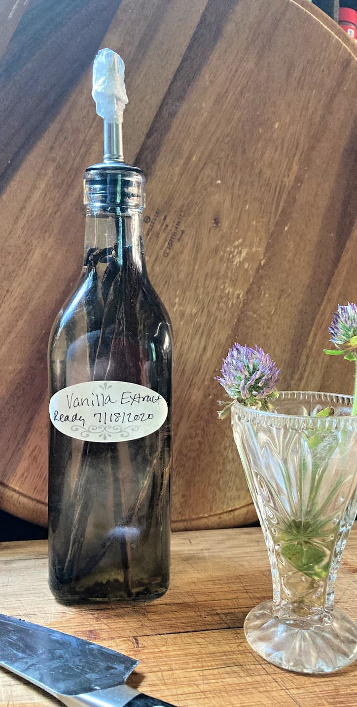 bottle of fresh made vanilla extract and flowers