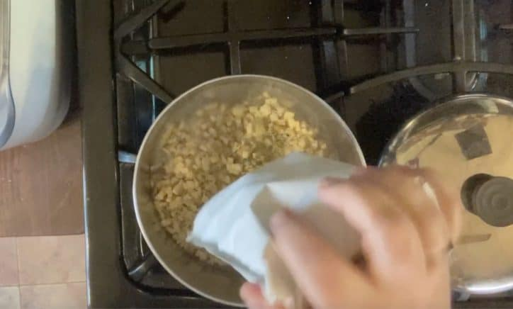 hand adding stuffing mix package to sauce pan