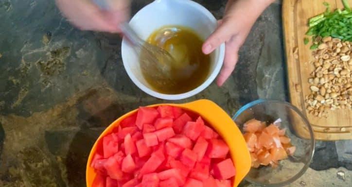 hand mixing dressing ingredients in white bowl