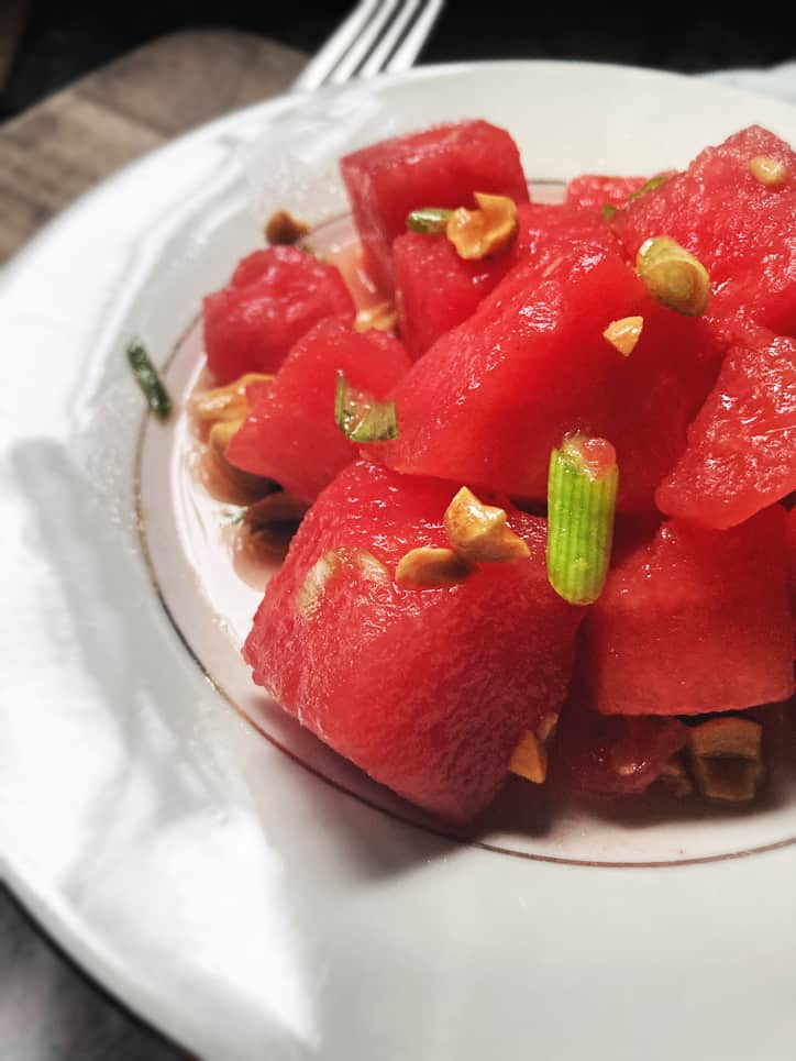 close up of watermelon grapefruit salad on a white plate