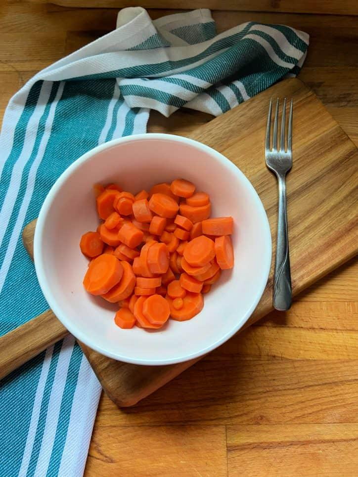 Sliced carrots in white bowl