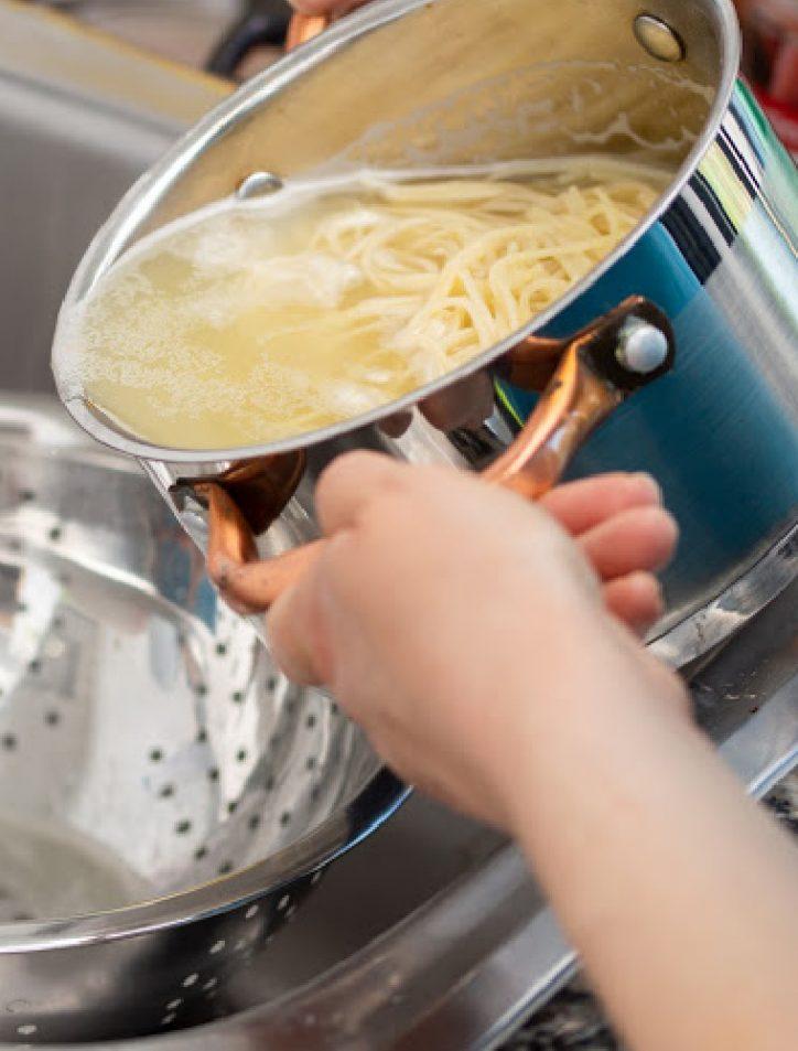 draining pasta into colander