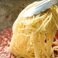 adding pasta to sauce