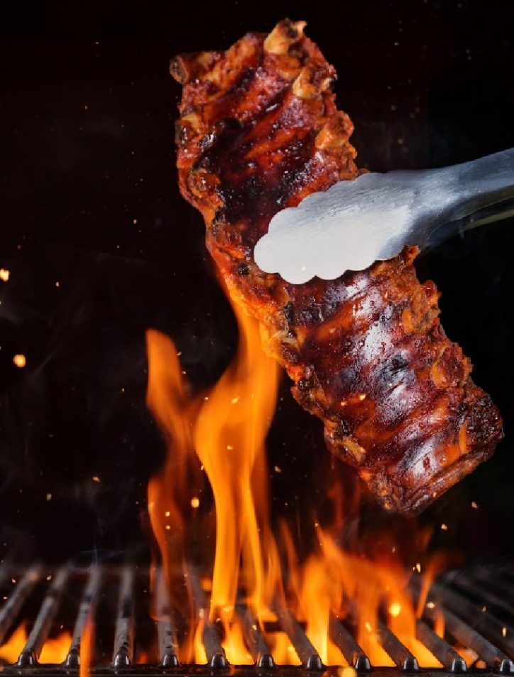 baby back ribs with tongs over fire